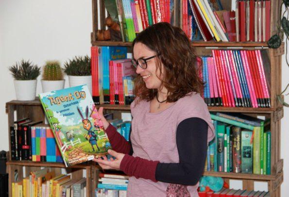 Kinderbuchautorin Katharina Mauder präsentiert eines ihrer Bilderbücher vor Regal voller Kinderbücher
