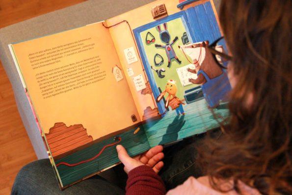 Katharina Mauder liest in einem ihrer Bilderbücher, um zu zeigen, dass Kinderbuchautor*innen nicht ohne Illustrator*innen auskommen.